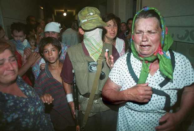 Закрывшие свои лица чеченские боевики Шамиля Басаева показывают журналистам женщин и детей, взятых ими в заложники при захвате больницы Фото: Эдди Опп / «Коммерсантъ»