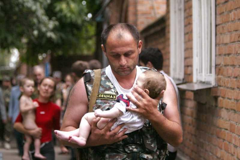 Милиционер Эльбрус Гогичаев выносит шестимесячную Алену Цкаеву из здания школы 2 сентября 2004 г.