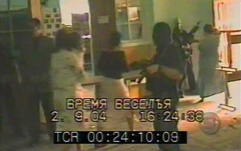 Аушев (крайний слева), террористы и заложники в здании школы 2 сентября 2004 г. Видеокамера попала в руки боевиков от одного из родителей, снимавших школьную линейку, отсюда и жутковатая надпись «время веселья»