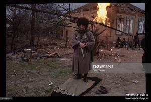 A Chechen Muslim man prepares to pray with fires burning behind him