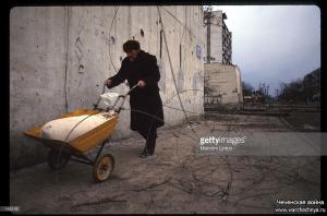 A Chechen civilian pushes a wheelbarrow January, 1995 in Russia