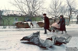 A Chechen couple, pulling a cart with their belongings, walk past missile debris on a Grozny street on January 26, 1995