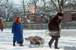A Chechen couple, pulling their belongings on a sled, walk past a burning house that was hit by Russian artillery in central Grozny on January 24, 1995