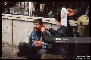 A Chechen fighter applies gauze to a wounded comrade January 13, 1995 in Russia2