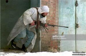 A Chechen fighter armed with a machine-gun dodges bullets as he changes his position during fighting in Grozny 26 January 1995