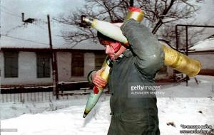 A Chechen fighter carries two shells on his way back to his position 26 January 1995