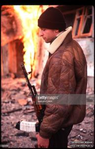 A Chechen fighter stands near a fire January 16, 1995 in Grozny, Russia