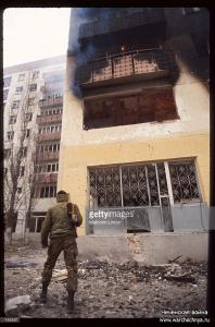 A Chechen fighter stands near the presidential palace January, 1995 in Grozny, Russia
