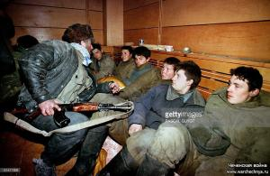 A Chechen figther holding his kalachnikov submachine guards 15 January several Russian soldiers who were captured during recent Russian offensive