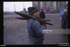 A Chechen guerrilla carries missiles for bazookas over to a van