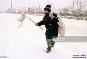 A Chechen holds a piece of white cloth as he crosses a snow-covered avenue in Grozny 23 january as Russian artillery continue their shelling on to Chechen capital
