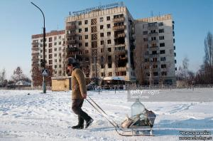 A Chechen man, looking for water, pulls a sled carrying, among other things, a large water bottle, past a war-ravaged building