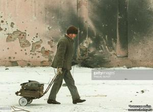 A Chechen refugee pulls a crate containing his belongings as he walks past a bullet and shell-riddled wall in Grozny 23 January