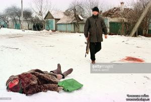 A Chechen soldier walks past the body of a woman killed by Russian artillery shelling 24 January in central Grozny