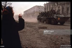 A Chechen woman watches a Russian armored personnel carrier January, 1995 in Grozny, Russia