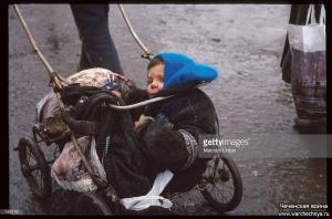 A child in a stroller is wheeled out of the shelling area January 13, 1995 in Grozny, Russia2