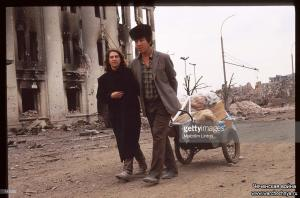 A couple pulls a cart past ruined buildings January, 1995 in Grozny, Russia