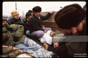 Chechen fighters sit with an injured comrade in the back of a truck January 13, 1995 in Grozny, Russia