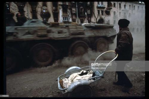 A Russian armored personnel carrier drives past a Chechen civilian January, 1995 in Grozny, Russia