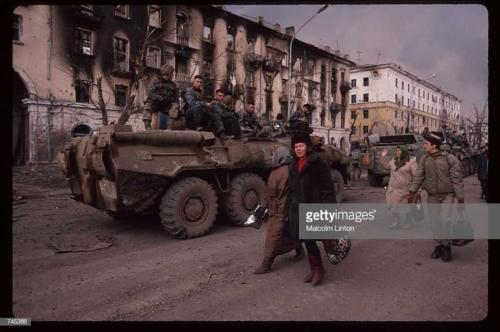 Chechen civilians walk past a Russian armored personnel carrier January, 1995 in Grozny, Russia
