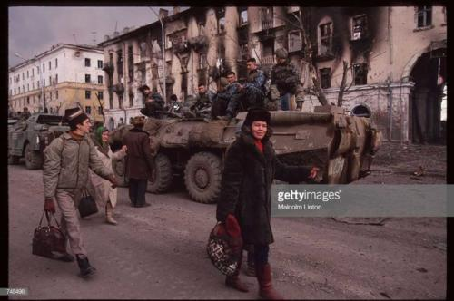 Chechen civilians walk past a Russian armored personnel carrier January, 1995 in Grozny, Russia2