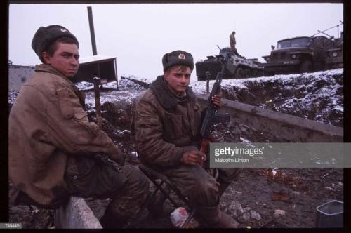 Russian interior ministry soldiers sit in the snow January, 1995 near Grozny, Russia