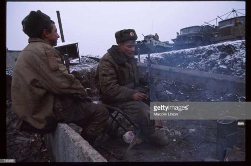 Russian interior ministry soldiers sit in the snow January 10, 1995 near Grozny, Russia