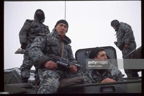 Russian interior ministry soldiers sit on top of an armored personnel carrier January, 1995 near Grozny, Russia