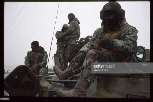Russian interior ministry soldiers sit on top of an armored personnel carrier January, 1995 near Grozny, Russia3