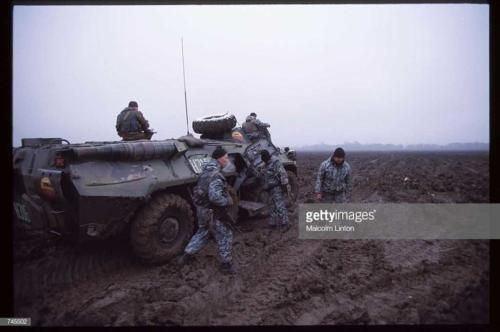 Russian interior ministry soldiers stand next to an armored personnel carrier January 10, 1995 near Grozny, Russia