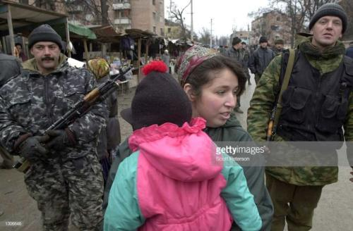 2 A Chechen woman carries her child ahead of Russian troops on patrol in central Grozny November 23, 2000, capital of the breakaway republic of Chechnya