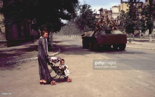 2 A Chechen woman walks her child in the streets of Grozny as Russian soldiers look on