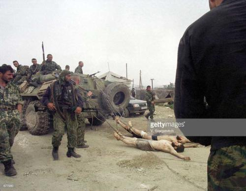 2 Russian Army forces drag dead Chechen fighters behind an armored personnel carrier September 1999 during operations in the village of Karamakhi, Dagestan