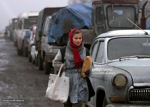 A Chechen girl carries a loaf of bread as she walks along a convoy of Chechen refugees queueing up to return to northern Chechnya at the Chechen-Ingush border check point 27 December 1999