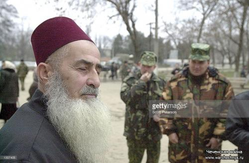 A Chechen man looks away from Russian soldiers November 22, 2000 in Gudermes, east of the Chechnya capital, Grozn