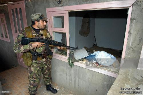 A Chechen soldier inspects 11 March 2005 a house in the Chechen village of Tolstoi-Yurt, where rebel leader Aslan Maskhadov