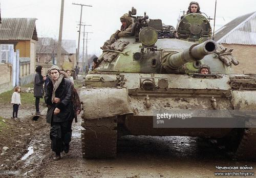 A Chechen woman passes by a tank of Russian federal troops on the main street of Gehy-Chu village, south from Grozny 16 February 2000