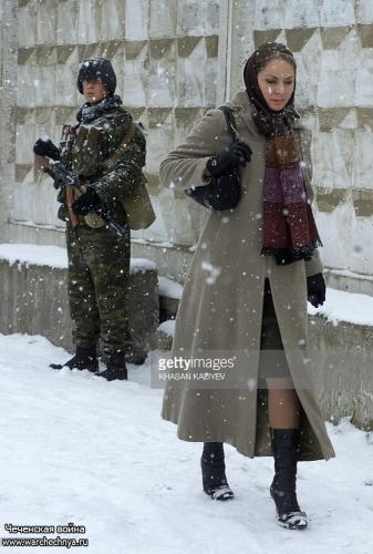 A Chechen woman walks past a Russian soldier during a heavy snowfall in Grozny 17 January 2006