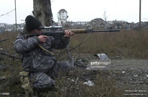 A Russian sniper takes aim in central Grozny November 23, 2000, capital of the breakaway republic of Chechnya