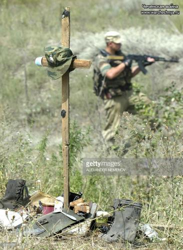 A Russian soldier controls 27 August 2003 an area outside Grozny behind a cross made to commemorate the place where nine Russian paratroopers were killed in their vehicle 21 August by Chechen guerrila
