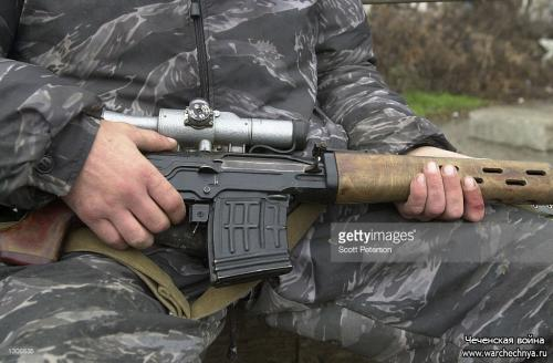 A Russian soldier cradles his gun November 23, 2000 while on patrol in Grozny, capital of the breakaway republic of Chechnya